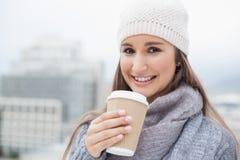 La morenita sonriente con invierno viste en sostener la taza de café Imágenes de archivo libres de regalías