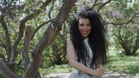 La morenita sonriente mira la cámara que se coloca cerca del árbol en el jardín almacen de metraje de vídeo