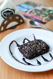 La morsure de 'brownie' de noix a servi dans un plat blanc avec la garniture de crème au chocolat images libres de droits