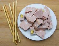 La mortadella bolognese incide i cubi su un piatto, con i grissini, tavola di legno immagine stock