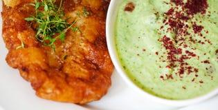 La morue frite dans la pâte lisse avec le concombre et le yaourt plonge, détaille Photographie stock libre de droits
