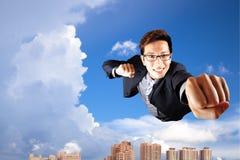 La mosca del hombre de negocios en cielo tiene gusto del supermán Imágenes de archivo libres de regalías