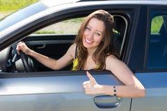 La mostra felice della donna buona firma dentro l'automobile Fotografia Stock