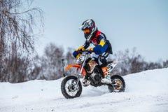 La moto de coureurs de petit garçon de plan rapproché monte par la voie couverte de neige de motocross Images stock