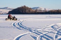 La moto de nieve con los pescadores no identificados está montando a lo largo del lago del invierno contra un fondo de una colina Fotografía de archivo libre de regalías