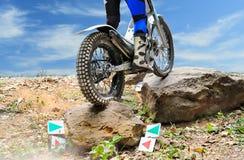La moto de procès saute par-dessus des roches photo stock