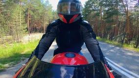 La moto está siendo conducida por una persona a lo largo del camino del pino almacen de video