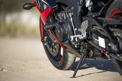 La moto rouge se tient sur une route arénacée images stock