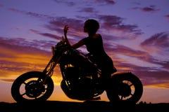 La motocicleta de la mujer de la silueta sienta el codo en el tanque Fotografía de archivo