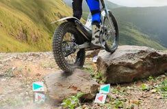 La motocicleta de los ensayos está saltando sobre rocas Imagen de archivo libre de regalías