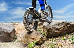 La motocicleta de los ensayos está saltando sobre rocas Foto de archivo