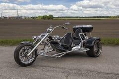 La motocicleta de tres ruedas se coloca en el estacionamiento cerca del campo fotos de archivo