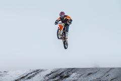 La motocicleta joven del corredor del muchacho vuela después de saltar sobre la montaña Imagenes de archivo