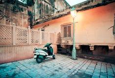 La motocicleta parqueó cerca del farol en calle vieja de la ciudad fotografía de archivo