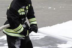 La mousse de alimentation d'un pompier tenu dans la main, mousse extinctrice vole hors du tronc, qui maintient le pompier dans le photographie stock libre de droits