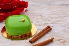La mousse de lustre gren le gâteau avec des bâtons de cannelle au-dessus des fleurs sèches rouges de witg en bois blanc de fond photo libre de droits