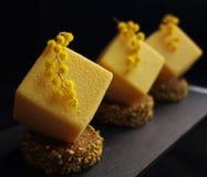 La mousse giallo arancione ha strutturato i dessert sulle fette della spugna del pistacchio con i fiori della mimosa fotografie stock libere da diritti