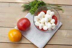 La mozzarella in una ciotola di vetro, pomodori, ha affettato i pomodori e le erbe su una tavola di legno Fotografia Stock