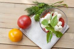 La mozzarella in una ciotola di vetro, pomodori, ha affettato i pomodori e le erbe su una tavola di legno Fotografie Stock