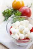 La mozzarella in una ciotola di vetro, pomodori, ha affettato i pomodori e le erbe su una tavola di legno Fotografia Stock Libera da Diritti