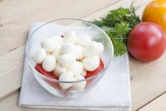 La mozzarella in una ciotola di vetro, pomodori, ha affettato i pomodori e le erbe su una tavola di legno Immagine Stock