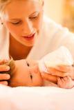 La mère alimente la chéri Image libre de droits