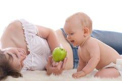 La mère donnent la pomme verte à son fils Photographie stock libre de droits