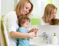 La mère enseigne les mains de lavage d'enfant dans la salle de bains Photos libres de droits