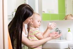 La mère enseigne les mains de lavage d'enfant dans la salle de bains Images stock