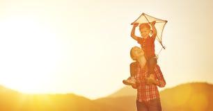 La mère et l'enfant heureux de famille courent sur le pré avec un cerf-volant dans le summe Photos stock