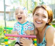 La mère heureuse avec le bébé riant s'assied sur l'oscillation Photographie stock libre de droits
