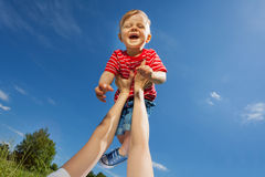 La mère soulève le fils riant avec les bras droits Photo stock