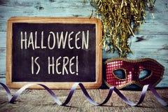 La máscara y el texto Halloween está aquí en una pizarra Imagen de archivo libre de regalías