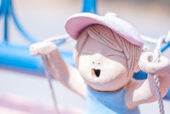 La muñeca de cerámica rosada linda de la muchacha está jugando el oscilación de la cuerda en el azul yo foto de archivo libre de regalías
