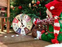 La muñeca de la Navidad se sienta cerca del árbol de navidad adornado Fotografía de archivo libre de regalías