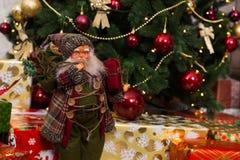 La muñeca de Santa Claus con una ruborización en las mejillas que sostienen un regalo se coloca Fotos de archivo libres de regalías
