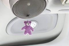 La muñeca púrpura del oso de peluche está colgando en los altavoces en el cuarto del coche foto de archivo libre de regalías