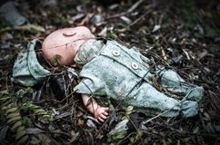 La muñeca rota vieja abandonada se descompone en bosque asustadizo Fotografía de archivo libre de regalías