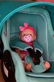 La muñeca se sienta en una silla del automóvil foto de archivo libre de regalías