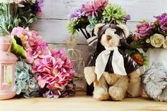 La muñeca y la vela lindas del peluche se encienden con el ramo de la flor Fotografía de archivo