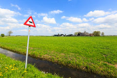 La mucca segnale di pericolo dentro un paesaggio olandese Fotografia Stock Libera da Diritti