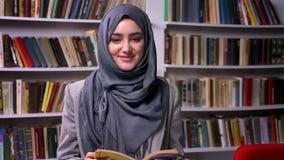 La muchacha árabe bonita agradable en hijab gris agradable se está colocando delante del estante de librería y está sonriendo en  almacen de metraje de vídeo