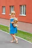 La muchacha 6 años con el terrier de Yorkshire en sus brazos acerca al edificio alto Imagenes de archivo