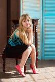 La muchacha 6 años en vestido se sienta en una silla cerca de la pared Foto de archivo
