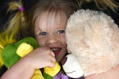 La muchacha abraza los juguetes y las risas de la felpa fotografía de archivo libre de regalías