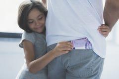 La muchacha abraza a su padre, sonríe astuto y mira el dinero que él intenta robar el suyo el bolsillo de la parte posterior Imagen de archivo