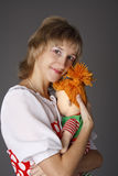 La muchacha abraza una muñeca Fotos de archivo