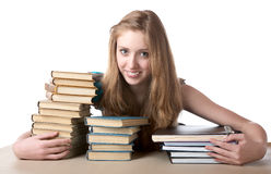 La muchacha abraza una pila de libros Imagen de archivo