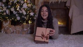 La muchacha abre la caja con un regalo y disfruta la mentira en el piso cerca del árbol de navidad 4K almacen de video
