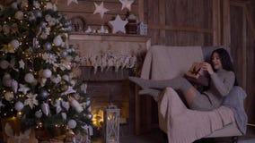 La muchacha abre la caja con un regalo y disfruta sentarse en una silla cerca del árbol de navidad el día de la Navidad 4K almacen de metraje de vídeo